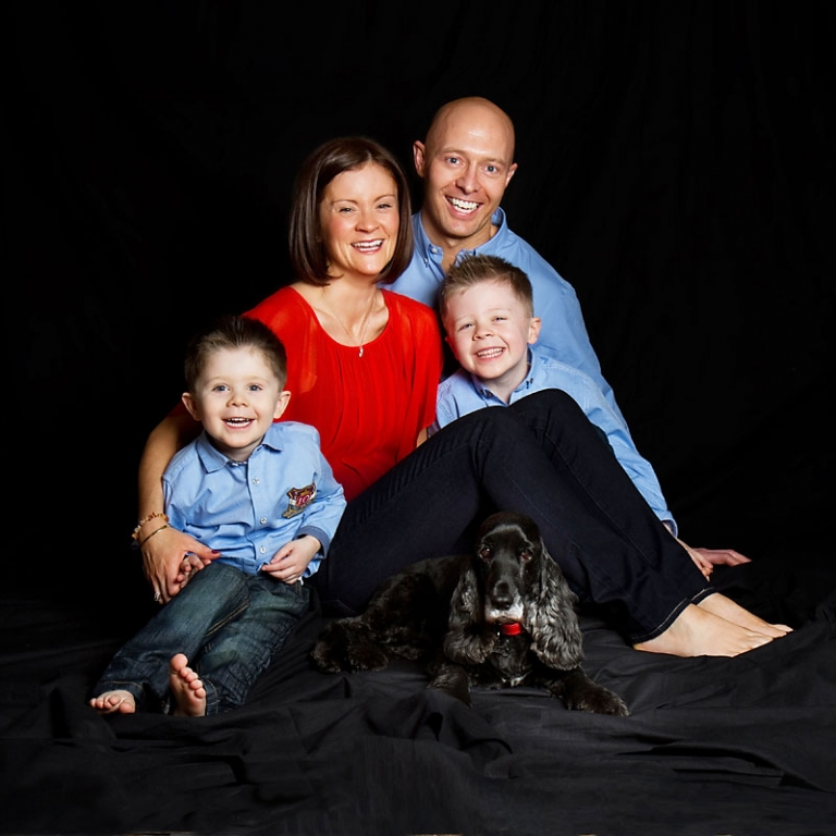 Image of family group - Mum, Dad, 2 boys & dog against black background.